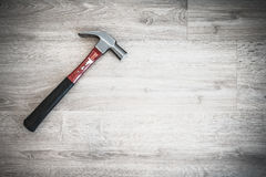 Red hammer on wooden floor, interior construction tool or home fixing renovation concept, dark tone abstract with vignette effect Stock Images