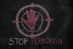 Red hand shape and stop terrorism text in the sign target on black chalkboard. Hand shape and stop terrorism text in the sign target drawn with red chalk on Stock Photos