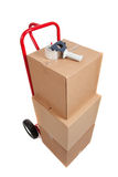 A red hand truck with boxes and a tape gun. A red hand truck/dolly on a white background with cardboard boxes and a tape gun Royalty Free Stock Photo