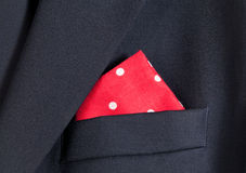 Red handkerchief in blue blazer. Folder linen handkerchiefs in red with white spots in top pocket of blazer stock image