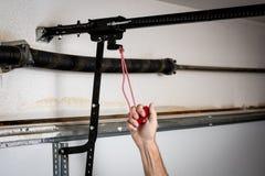 Man pulls red quick release for a garage door opener. Red handle that release a garage door from opener stock photography