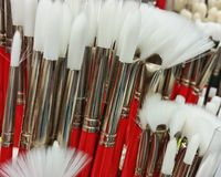 Red handled paint brushes. White tipped red handled art brushes on display for sale royalty free stock photos