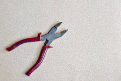 Red handled pliers on wood background Stock Photography