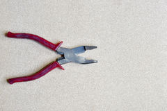 Red handled pliers on wood background Stock Photo