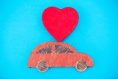 Red handmade car delivery with heart shape toy. On blue background Royalty Free Stock Images