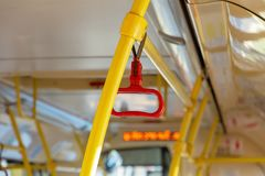 Red handrails in an empty bus. Safety in Urban Ground Public Transport stock photography
