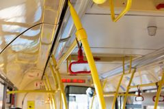 Red handrails in an empty bus. Safety in Urban Ground Public Transport stock image