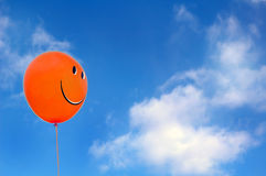 Red happy face balloon with blue sky athe background. Red happy face balloon with blue sky and white clouds at the background royalty free stock photography