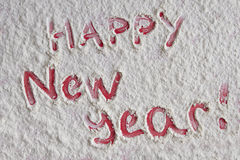 Red Happy new year written on white flour background Royalty Free Stock Image