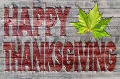 Red Happy Thanksgiving written on wooden board background with green leaf Stock Images
