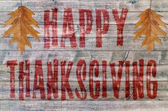 Red Happy Thanksgiving written on wooden board background with two leaf Stock Photography