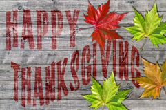 Red Happy Thanksgiving written on wooden board and colorful leaf. Close Stock Photos
