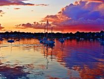Red Harbor Water and Sky at Sunset. The sun cast multi colors across storm clouds and harbor waters stock photo