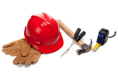 A red hard hat and leather work gloves with tools Royalty Free Stock Photography