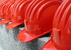 Red hard hats. A row of red hard hats (safety helmets for protection&#x29 Stock Images
