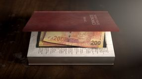 Concealed Notes In A Book. A red hardback book with a cutaway area in the pages concealing a stack of rand notes on an isolated background Stock Image