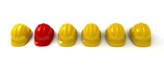 Red hardhat among yellow ones Stock Photo