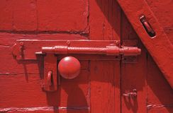 Red hardware. A close up detail shot of a red door showing a latch,knob,and hardware all high gloss paint Royalty Free Stock Photography