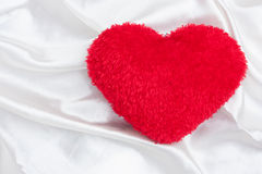 Red hart. On white cotton background stock photos