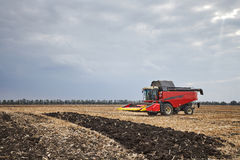 Red harvester working in a field Stock Photo