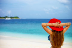 Red hat on the beach. A Woman in Red Hat standing on the beach looking at the yacht on the horizon Stock Image