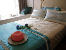 Red hat on the bed. Interior of a fashion bedroom with a red hat on the bed Stock Image