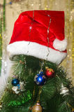 Red hat on a Christmas tree. Wearing a red hat on top of Christmas tree Stock Photo