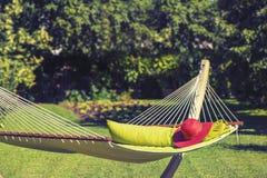 Red Hat en una hamaca en el jardín Imagen de archivo libre de regalías