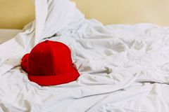 Red hat on the left side over white blanket on the bed with yellow background stock image