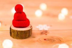 Red hat on a piece of wood with lights and a snowflake royalty free stock images