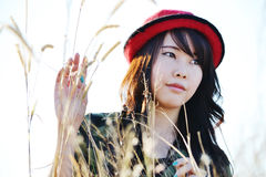 Red hat pretty girl01. Thai pretty girl wear the red hat in meadow Royalty Free Stock Image
