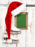 Red hat for Santa Claus and white ice skates. Vintage chalkboard Royalty Free Stock Photography
