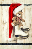 Red hat, Teddy Bear and ice skates. Vintage christmas decoration Stock Photos