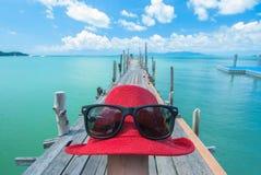 Red Hat und Sonnenbrille auf Meer, Meer und blauem Himmel Lizenzfreie Stockbilder