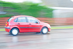 Red hatchback car driven in the rain. A n image of a red car being driven in the rain and captured using a panned shot. The image is purposely blured to royalty free stock photo