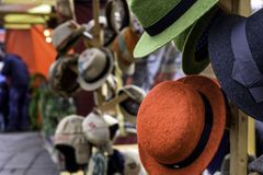 Red Hats Berlin Market. Group of colored hats for sale, hanging on a wall Market stock photo