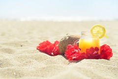 Red Hawaiian lei garland on the beach. Red Hawaiian lei garland with juice in a jar and coconut on sand on the beach, with ocean on background. Perfect vacation Stock Images