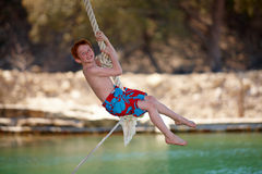 Red head boy swinging on rope. Red head boy in swimming suit swingging on rope above lake Royalty Free Stock Image
