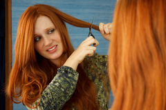 Red head cut hair. Pretty red head girl nervously cutting hair in mirror Stock Photo