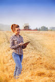 Red-head farmer girl accounting the crop in wheat field. Red-head farmer girl in glasses with hair tied in a ponytail keeps a crop accounting on the tablet in Royalty Free Stock Photos