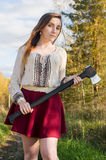 Red head girl with axe in the forest Stock Photo