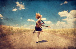 Red-head girl with guitar. Photo in old image style. Stock Photos