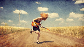 Red-head girl with guitar. Photo in old image style. Royalty Free Stock Image