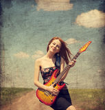 Red-head girl with guitar. Photo in old image style. Stock Photo