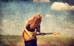 Red-head girl with guitar. Photo in old image style. Stock Photography