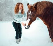 Red head girl with a horse in a field of snow in winter. royalty free stock images