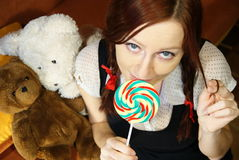 Red head girl with lollipop and teddy bears. Portrait of young woman with red haier with lollipop and teddybears Royalty Free Stock Photo