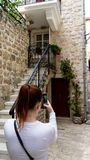 Red head girl taking a picture in the stone narrow streets of a town in the adriatic coast. Woman making photo with smart phone to royalty free stock photos