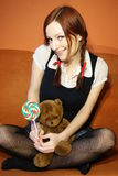 Red head girl and teddy bear. Red head young womanwith lollipop and teddy bear Royalty Free Stock Images