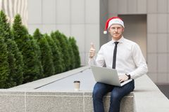 Red head man in santa hat, working outdoor, thumbs up and looking at camera. Stock Photography